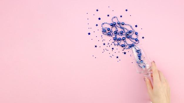 Canutiglia blu in un vetro sul fondo e sulla mano rosa dello spazio della copia Foto Gratuite