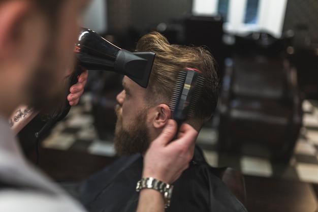 Capelli del cliente che asciugano il barbiere senza volto