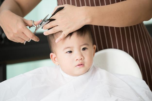 Capelli di taglio del neonato dalla sua mamma a casa Foto Premium