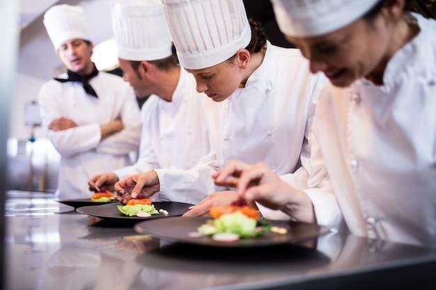 Capo chef che si affaccia sull'altro cuoco che prepara il piatto Foto Premium