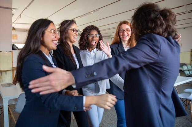 Capo squadra che abbraccia i suoi colleghi più giovani felici Foto Gratuite