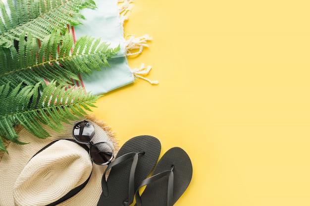 Cappellino da spiaggia in paglia, occhiali da sole, infradito su giallo Foto Premium