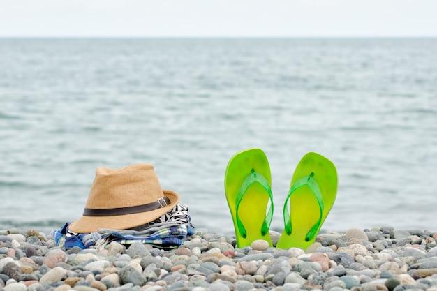 Cappello, abbigliamento e infradito sulla spiaggia di ciottoli. Foto Premium