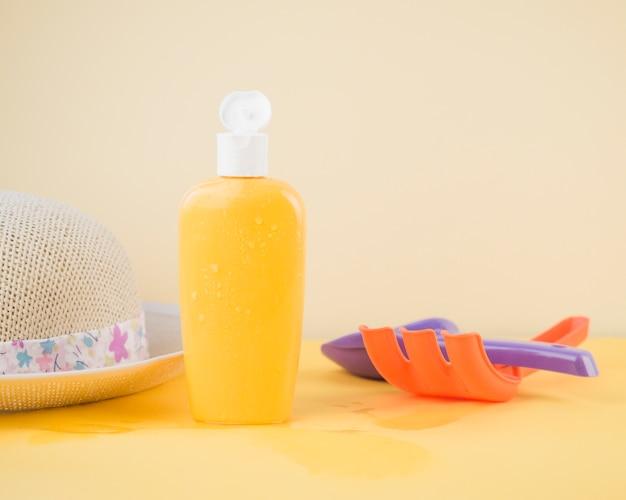 Cappello da sole; bottiglia di protezione solare; rastrello e pala giocattolo contro sfondo colorato Foto Gratuite