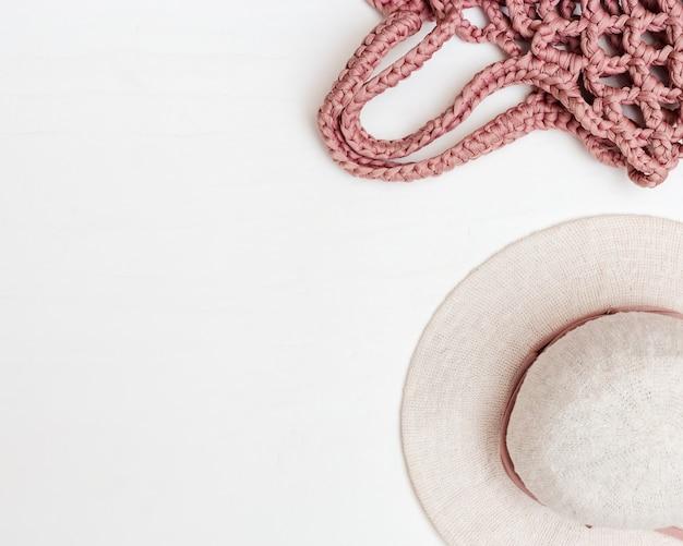 Cappello della donna della spiaggia e borsa fatta a mano rosa su fondo in cemento chiaro. vista dall'alto. copia spazio Foto Premium
