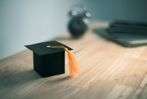 Cappello di laurea del mestiere del documento di costruzione sullo scrittorio di legno Foto Premium