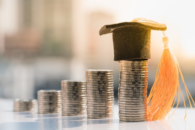 Cappello di laurea in cima pila di monete. Foto Premium