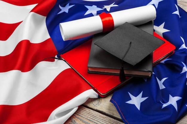 Cappello di laurea sulla bandiera degli stati uniti, concetto di educazione Foto Premium