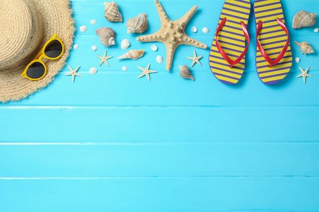 Cappello di paglia, occhiali da sole, infradito e molte stelle marine su fondo di legno di colore, spazio per testo e vista dall'alto. concetto di vacanze estive Foto Premium