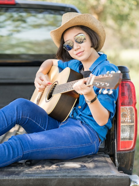 Cappello di usura della donna e suonare la chitarra sul camioncino Foto Premium