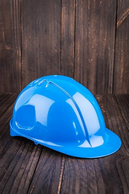 Cappello duro della costruzione su fondo di legno Foto Gratuite