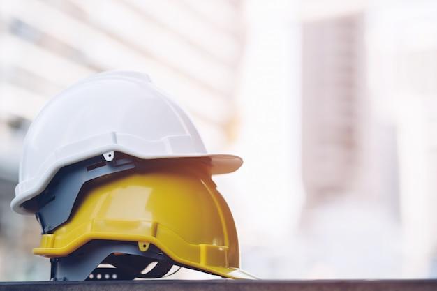 Cappello duro giallo e bianco del casco di usura di sicurezza nel progetto alla costruzione del cantiere sul pavimento di calcestruzzo sulla città Foto Premium