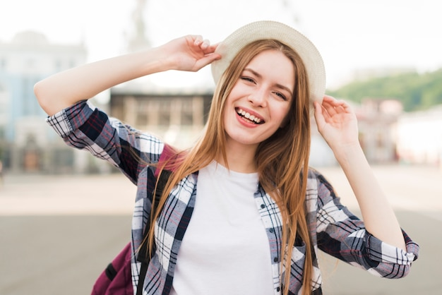 Cappello e posa abbastanza sorridenti della tenuta della donna Foto Gratuite
