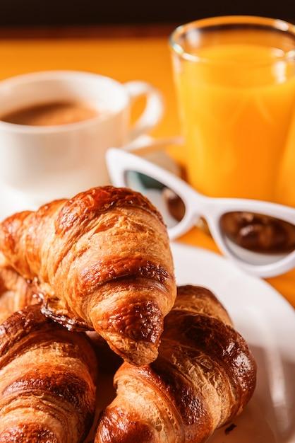 Cappello, occhiali da sole croissant con una tazza di caffè e un bicchiere di succo d'arancia su un tavolo giallo al sole Foto Premium