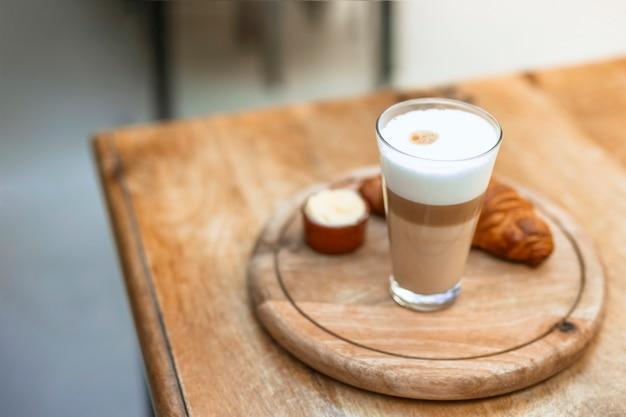 Cappuccino in vetro con croissant su vassoio circolare in legno Foto Gratuite