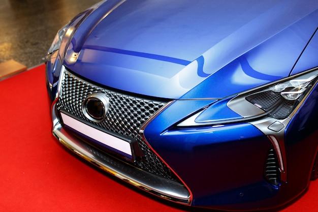 Cappuccio blu curvo dell'automobile sportiva che mostra una riflessione astratta. Foto Gratuite