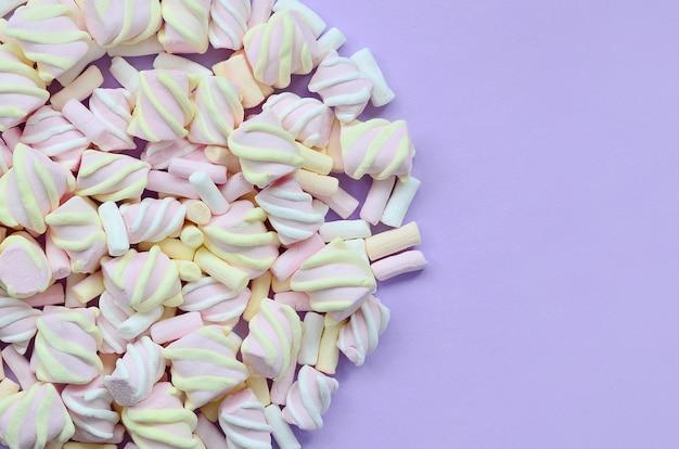 Caramella gommosa e molle variopinta presentata su fondo di carta viola. struttura creativa pastello. minimo Foto Premium