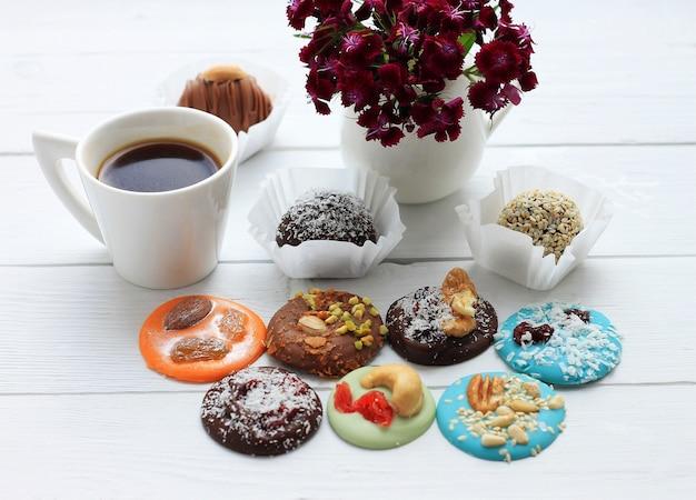 Caramelle al cioccolato, una tazza di caffè e un mazzo di fiori per san valentino su legno Foto Premium