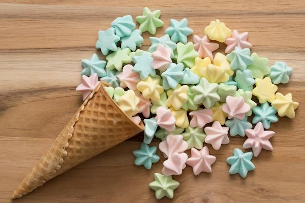 Caramelle color caramella sul cono gelato. fondo in legno Foto Premium