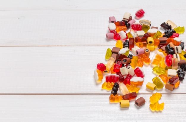 Caramelle colorate su fondo in legno Foto Premium