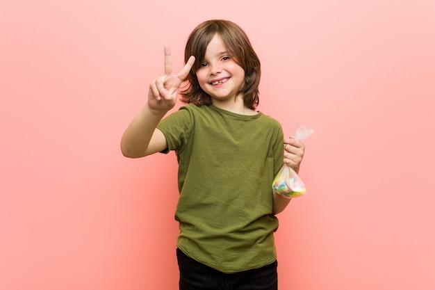 Caramelle della tenuta del ragazzino che mostrano numero due con le dita Foto Premium