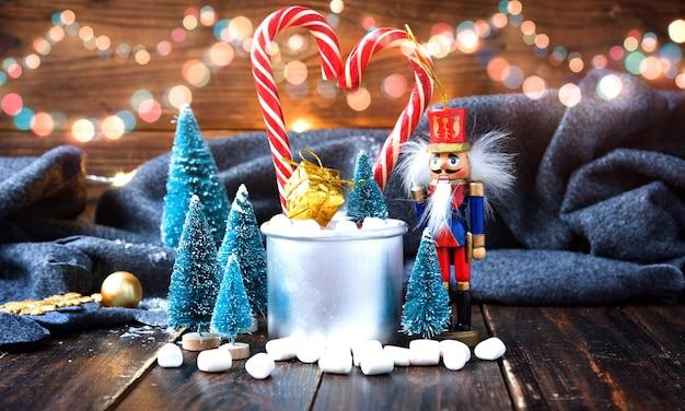 Caramelle gommosa e molle di natale e decorazioni del nuovo anno sulla tavola di legno con il plaid grigio. vacanze invernali Foto Premium