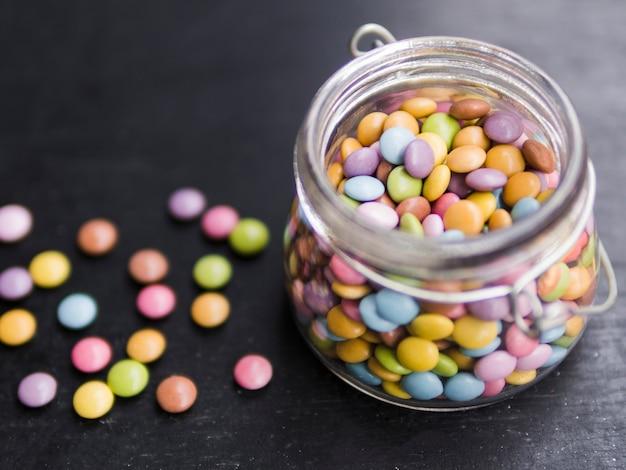 Caramelle smaltate multicolore in barattolo di vetro Foto Gratuite
