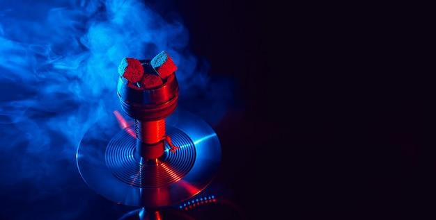 Carboni di shisha roventi in una ciotola del narghilé del metallo contro una priorità bassa di fumo Foto Premium