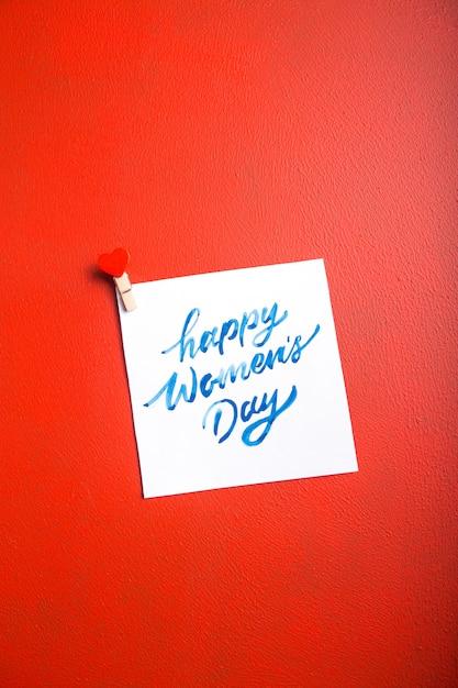 Cardi il messaggio con il giorno delle donne felici sulla tavola rossa Foto Premium