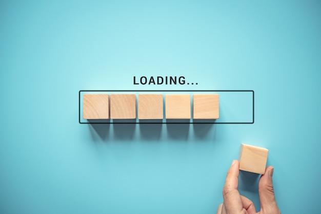 Caricamento, inserimento manuale del cubo di legno nella barra di avanzamento. Foto Premium