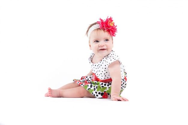 Carino bella bambina in abito a punto con farfalle e involucro rosso Foto Premium