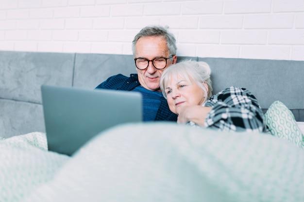 Carino coppia di anziani a letto con il portatile - Letto portatile ...