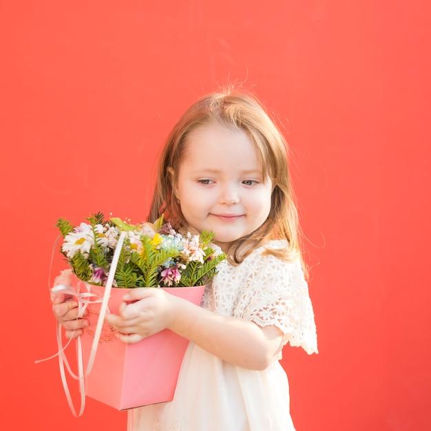 Carino damigella d'onore litte che tiene i fiori Foto Gratuite