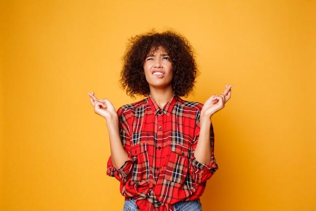 Carino femmina nera emotiva incrocia le dita, spera che tutti i desideri si avverino su sfondo arancione brillante. persone, linguaggio del corpo e felicità. Foto Gratuite
