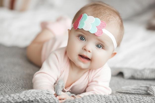 Carino piccolo bambino a casa in camera da letto. un bambino in casa. ritratto del bambino del 6 ° mese. adorabile bambina carina. Foto Premium