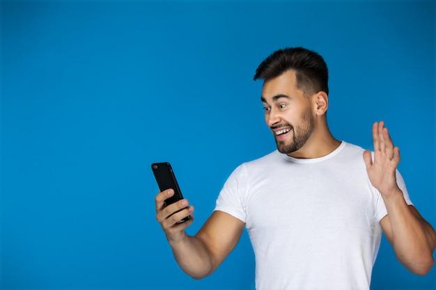 Carino uomo europeo sorride al telefono e agita la mano Foto Gratuite
