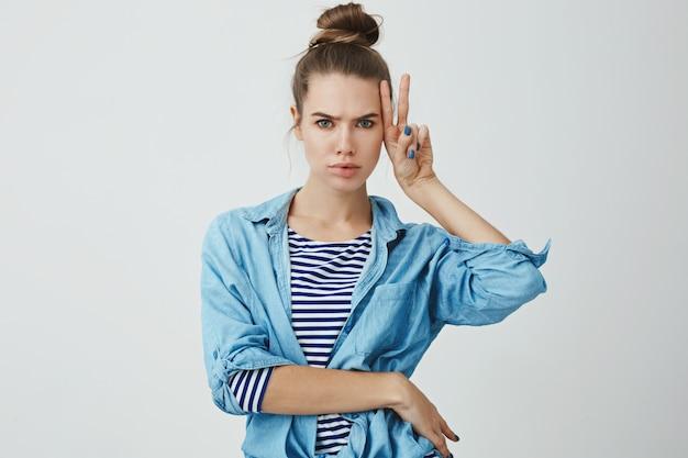 Carismatica attraente sexy giovane donna caucasica bun acconciatura che rende lunatico serio carino carino forte mostrando pace, segno fortunato accigliato, smorfie divertendosi, in posa Foto Gratuite