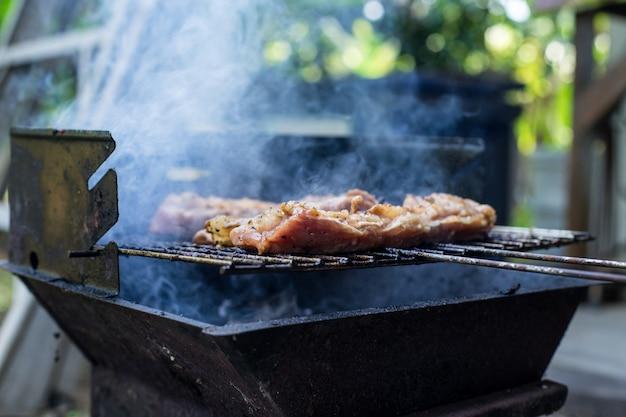 Carne alla bistecca di maiale all'aperto sulla griglia del barbecue, fatta in casa, carne di maiale fatta in casa Foto Premium