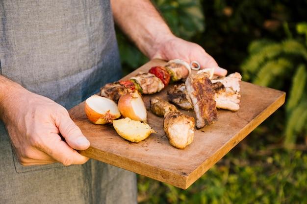 Carne alla griglia e verdure sullo scrittorio di legno in mani Foto Gratuite