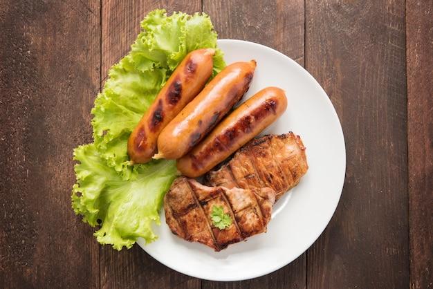 Carne alla griglia, salsicce e verdure sul piatto. Foto Premium