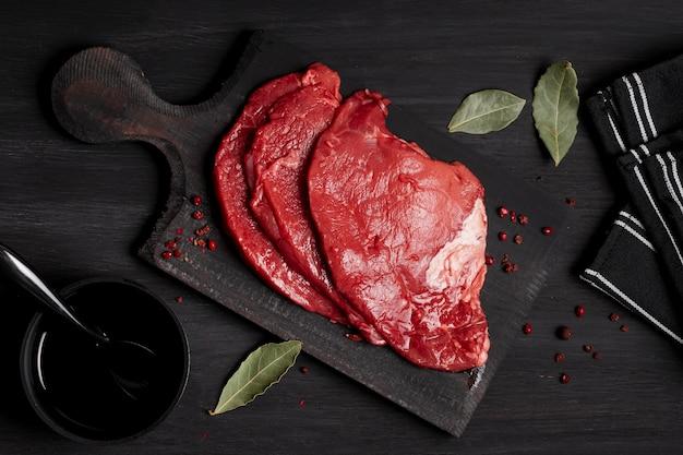 Carne cruda fresca sul bordo di legno con salsa di soia Foto Gratuite