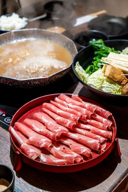 Carne di maiale affettata per il giapponese shabu shabu e sukiyaki Foto Premium