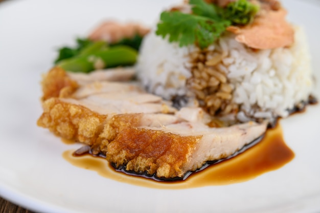 Carne di maiale croccante su un piatto bianco condita con salsa. Foto Gratuite