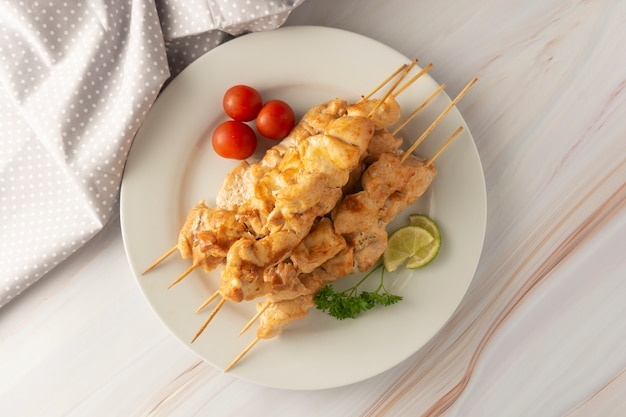 Carne di pollo sul kebab di bambù degli spiedi in piatto bianco, fondo luminoso di marmo. dieta a basso contenuto di grassi alimentari. Foto Premium