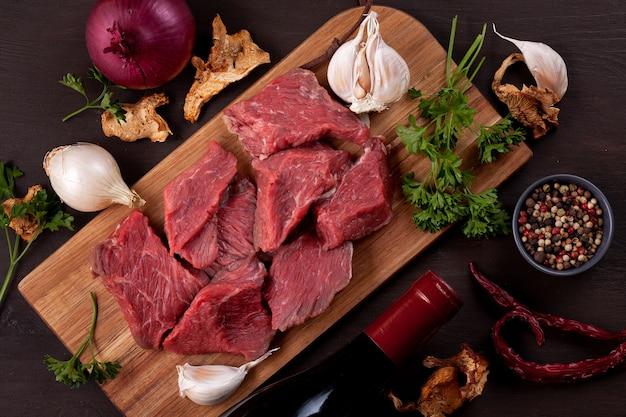 Carne fresca cruda, bottiglia di vino e verdure organiche di autunno stagionale sul bordo di legno pronto per cucinare Foto Premium