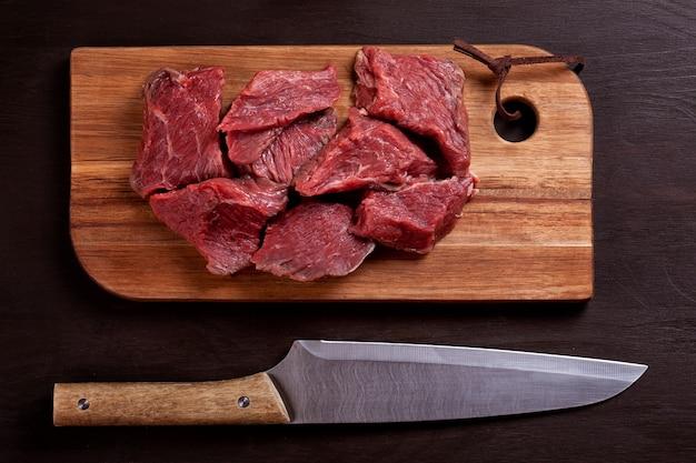 Carne fresca cruda sul bordo di legno pronto per cucinare Foto Premium