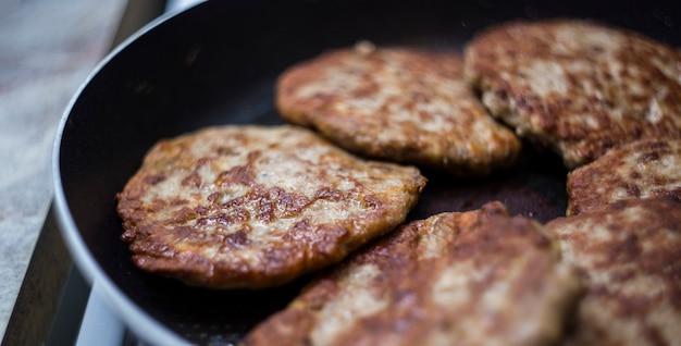 Carne fritta in padella cotolette di manzo fritte per hamburger. come fare un hamburger. Foto Premium