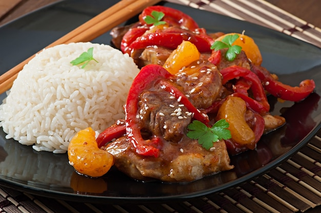 Carne in salsa piccante, peperoni e mandarini con contorno di riso bollito Foto Premium