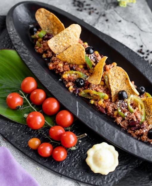 Carne macinata servita con olive al pepe di mais e tortilla chips Foto Gratuite