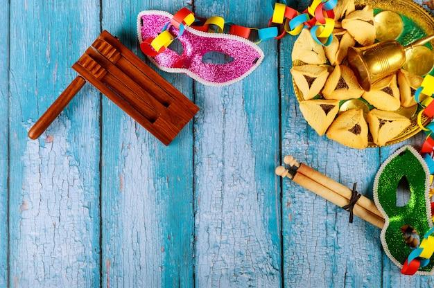 Carnevale ebraico purim celebrazione su biscotti hamantaschen, fabbricatore di rumori e maschera con pergamena Foto Premium